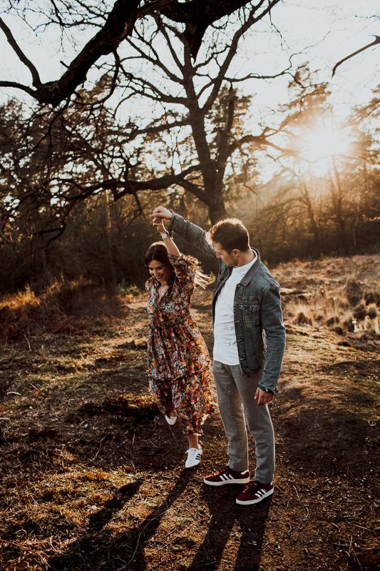 Die Frischverliebten tanzen in der Wildnis. Das goldene Licht zum Sonnenuntergang ist einfach perfekt für ein Jahrestagshooting.
