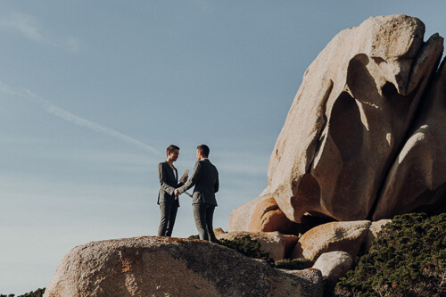 Spiritual Wedding on a rock, the same sex couple hold their hands during the wedding vow. It was so magic.