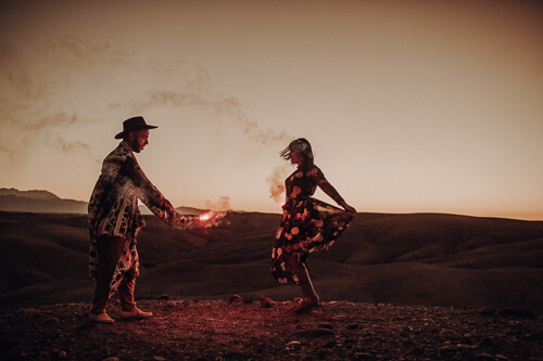 A super couple in love dances with a smoke torch in the desert of Morocco. It's a magical moment.