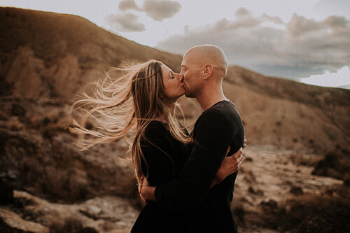 The wind storms while they kiss wildly. The shooting take place in Tabernas in Spain.