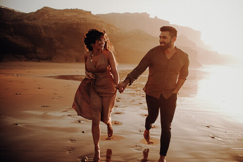 Happy couple running on the beach. They are incredibly in Love.