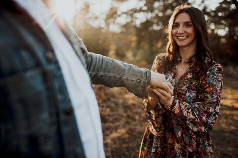 Die Frau hält die Hand des Mannes und lächelt ihn glücklich und verliebt an. Die Beiden befinden sich in einer Heidelandschaft und die Sonne taucht die Szenerie in ein goldenes Licht.