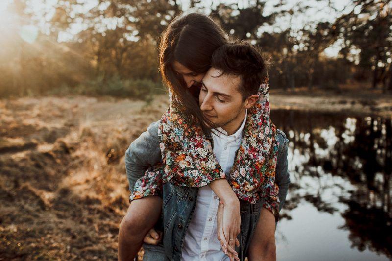 Der Mann hat seine Liebste Huckepack genommen, sie schmiegt sich ganz innig an ihn. Dieser Platz eignet sich hervorragend für ein magisches Elopement, speziell zum Sonnenuntergang.