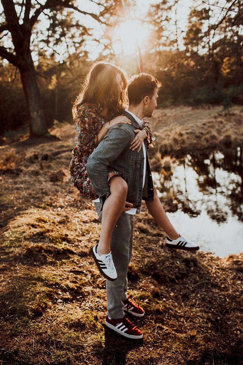 Er hat seine Liebste Huckepack genommen, die Beiden schauen ganz fasziniert auf den See, der sich im Sonnenuntergangslicht wunderschön spiegelt. Das goldene Licht ist einfach wundervoll. Diese Heidelandschaft ist einfach traumhaft und eine perfekte Kulisse für Sonnenuntergangsbilder.